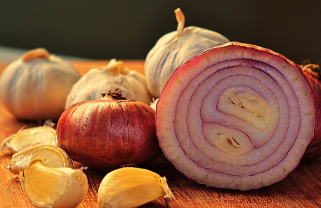 Chopping onions and garlic for seasonal beany vegetable hotpot by Katie Rushworth